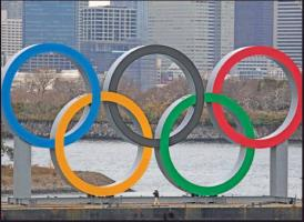 A WORKER is dwarfed by the Olympics Rings on a barge Friday in the Odaiba district of Tokyo. (AP Photo)