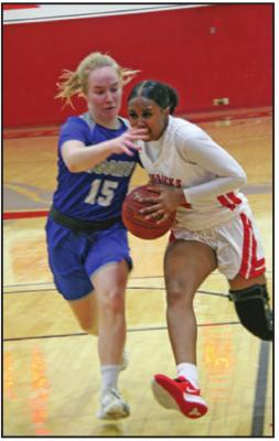 DRIVING TO the basket is Northern Oklahoma-Tonkawa's Chideyah Guyton (white uniform) during a game against Murray State in Tonkawa. Guyton scored 16 points, but Murray won the game 89-65. (News Photo by David Miller)