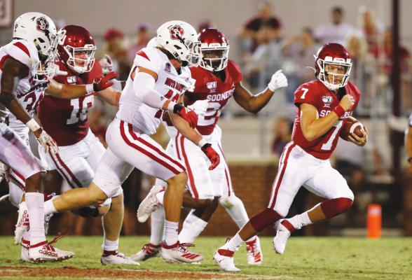 IN THIS Saturday, Sept. 7, 2019 file photo, Oklahoma quarterback Spencer Rattler (7) carries in the fourth quarter of an NCAA college football game against South Dakota, in Norman, Okla. Rattler is competing with Tanner Mordecai for the starting spot. (AP Photo/Sue Ogrocki, File)