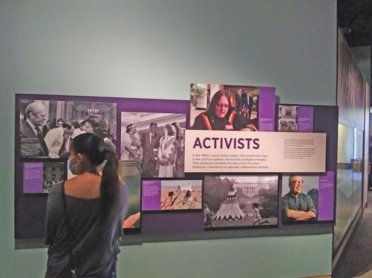 "A young woman observes the ""Activists"" collage on the fourth floor of the National Museum of the American Indian in Washington, D.C. ""Activists"" include Ladonna Harris, Reuben A. Snake, Suzan Shown Harjo, and Vine Deloria Jr. Photo courtesy Gaylord News / Jessie Christopher Smith"