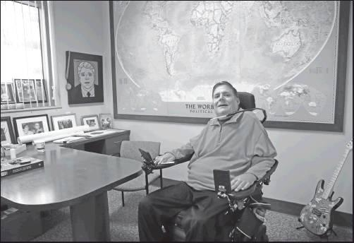 MARC BUONICONTI, who was paralyzed from the shoulders down making a tackle in college in 1985, poses Wednesday for a portrait in his office at the The Miami Project to Cure Paralysis in Miami. As the Super Bowl returns to Miami this week, Marc has mixed feelings about the sport. (AP Photo)