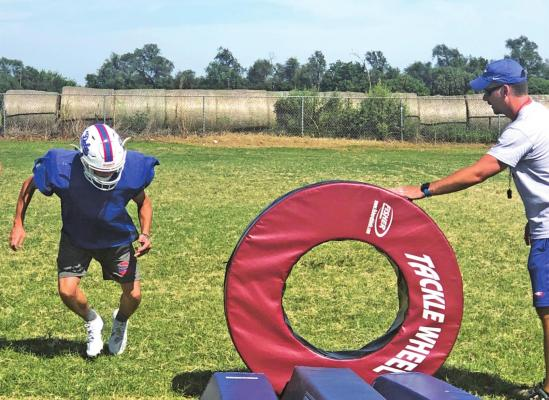 A DEER CREEK-LAMONT player participates in a tackling drill during a recent practice session in Lamont. Coach Justin Schanbacher is at right.