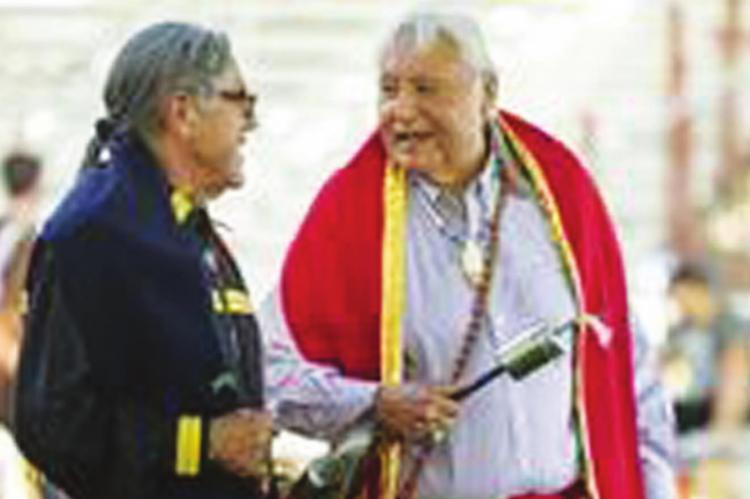 CITIZEN Potawatomi NationTribal Judge Phil Lujan, left, and Burt Patadal laugh together while leaving the arena after a gourd dance at the June 2019 Family Reunion Festival. Photo provided by CPN.