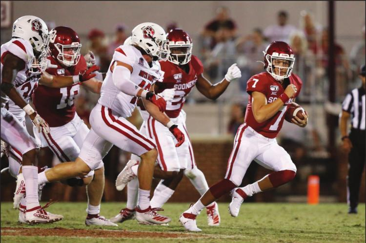 IN THIS Sept. 7, 2019 file photo, Oklahoma quarterback Spencer Rattler (7) carries in the fourth quarter of an NCAA college football game against South Dakota, in Norman, Okla. The coronavirus pandemic has shut down much of Division I football, but with three of the Power Five leagues still playing, there are still some big games to look forward to. Oklahoma takes on Texas on Oct. 10, 2020. (AP Photo/Sue Ogrocki, File)