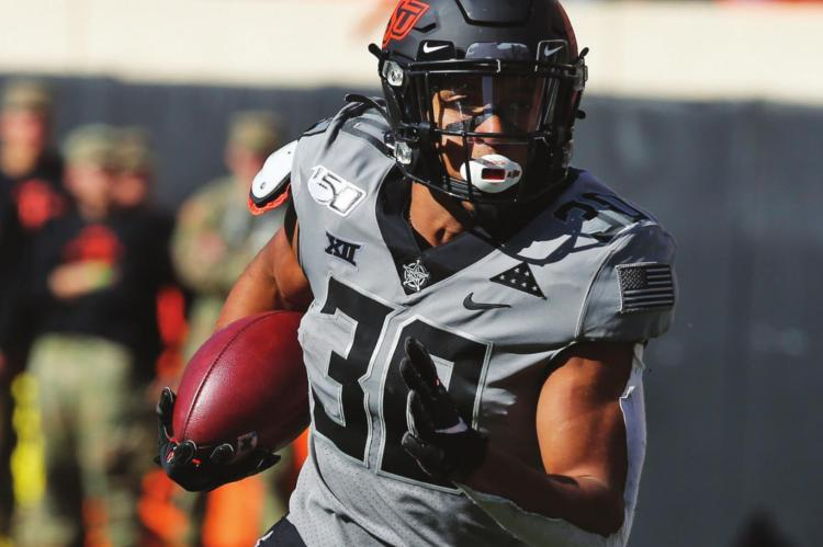 IN THIS Saturday, Nov. 16, 2019, file photo, Oklahoma State running back Chuba Hubbard (30) carries against Kansas during an NCAA college football game in Stillwater, Okla., Saturday, Nov. 16, 2019. Oklahoma State has high hopes with Heisman contender Chuba Hubbard and star receiver Tylan Wallace. (AP Photo/Sue Ogrocki)