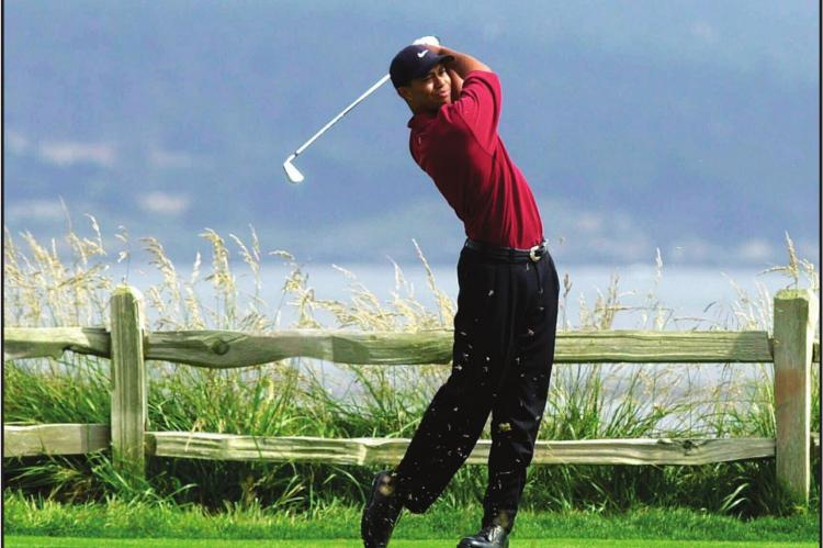 IN THIS JUNE 18, 2000, file photo, Tiger Woods tees off on the 18th hole on his way to winning the 100th U.S. Open Golf Championship at the Pebble Beach Golf Links in Pebble Beach, Calif. Golf Channel is airing a one-hour special on May 24 of Woods winning all four majors in a span of 10 months. (AP Photo/Elise Amendola, File)