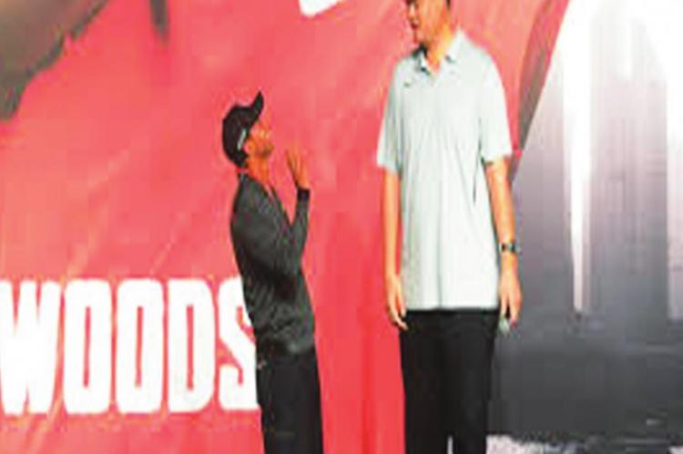 YAO MING, because of his imposing 7-foot-6 height, has been a favorite commercial subject. Here his height is on display standing near golfer Tiger Woods.