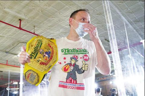 JOEY CHESTNUT poses after he won the 2020 Nathan's Hot Dog Eating Contest at Coney Island. He set a record by eating 75 hot dogs in 10 minutes.
