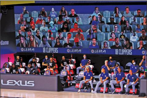 A view of the Los Angeles Clippers bench and fans on a screen during the game against the Phoenix Suns on August 4, 2020 at The Arena at ESPN Wide World of Sports Complex in Lake Buena Vista, Florida. (Kevin C. Cox/Getty Images/TNS)