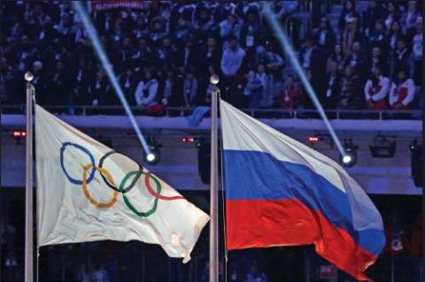THE RUSSIAN NATIONAL flag, right, flies after next to the Olympic flag during the closing ceremony of the 2014 Winter Olympics in Sochi, Russia. The World Anti-Doping Agency banned Russia on Monday from the Olympics and other major sporting events for four years, though many athletes will likely be allowed to compete as neutral athletes. (AP Photo)