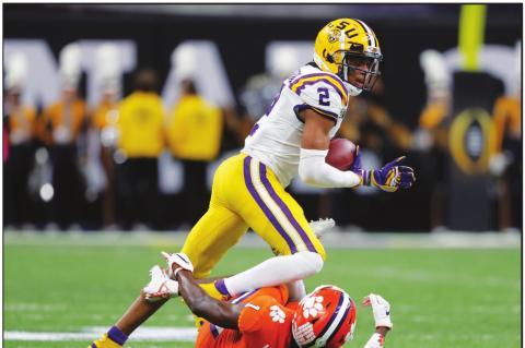 LSU WIDE receiver Justin Jefferson runs over Clemson cornerback Derion Kendrick during the first half of a NCAA College Football Playoff national championship game Monday, Jan. 13, 2020, in New Orleans. (AP Photo)