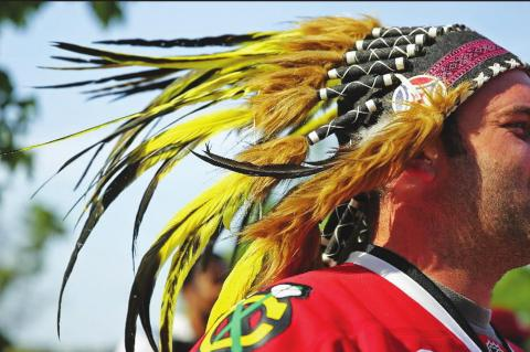A BLACKHAWKS FAN wears a fake Native American headdress before Game 2 of the 2013 Stanley Cup Final at the United Center.