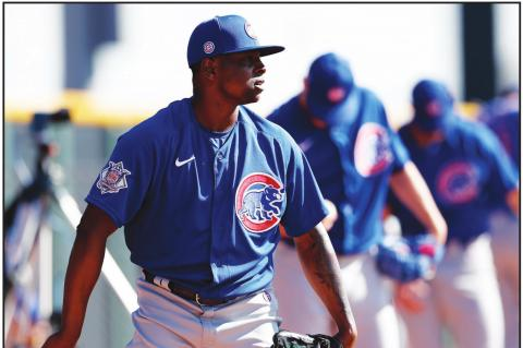 CHICAGO CUBS pitcher Jharel Cotton, left, throws alongside other pitchers during a spring training baseball workout Wednesday, Feb. 12, 2020, in Mesa, Ariz. (AP Photo)